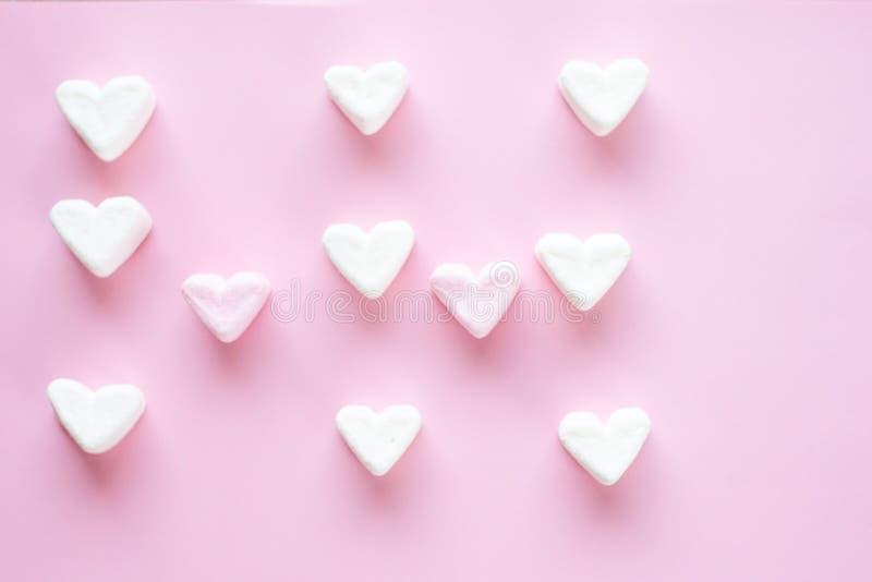 以心脏的形式蛋白软糖在样式计划的桃红色背景 E r 库存照片