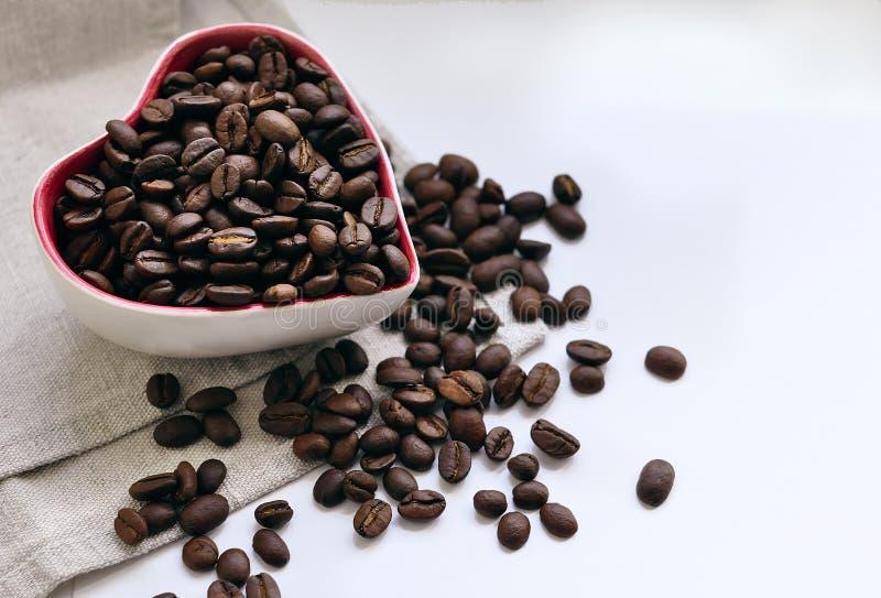 以心脏的形式,咖啡豆涌入了一小杯 图库摄影