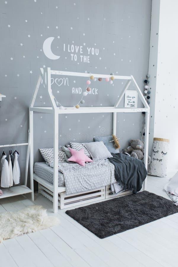 以房子的形式儿童` s时髦的床 有灰色枕头和床罩的斯堪的纳维亚样式男孩` s卧室在手工制造床上和 免版税库存照片