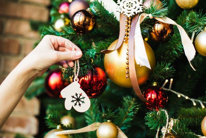 以手套的形式,女性手在圣诞树木玩具垂悬 免版税库存图片