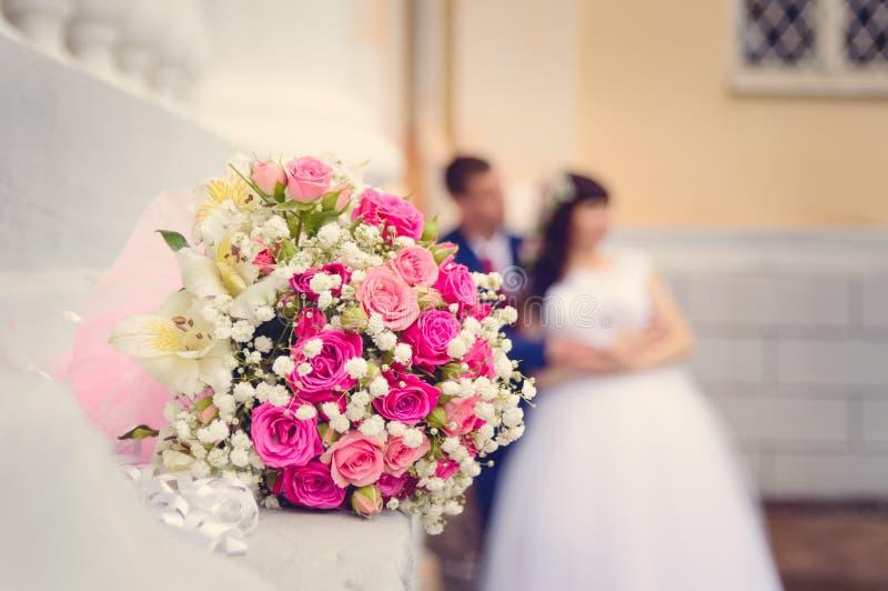 以新娘和新郎为背景的一个婚姻的花束特写镜头在他们的婚礼那天 定调子仿照instagram样式 库存图片