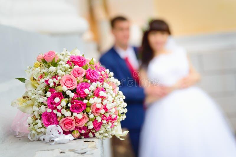 以新娘和新郎为背景的一个婚姻的花束特写镜头在他们的婚礼那天 库存照片
