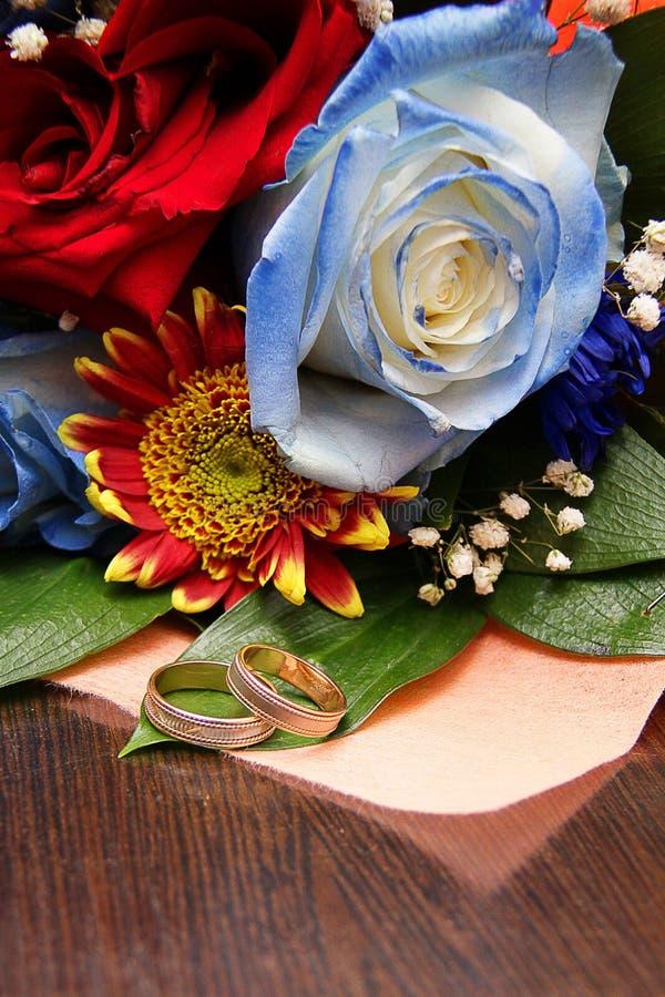 以新娘花束为背景的两结婚戒指从一朵蓝色玫瑰和红色 免版税库存照片