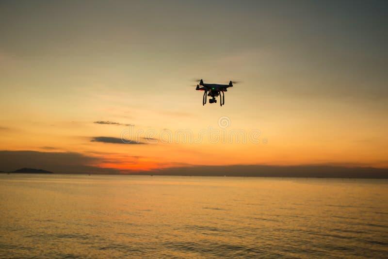 以日落为背景的剪影寄生虫 在晚上天空的飞行寄生虫 与数字照相机的Uav寄生虫 库存照片