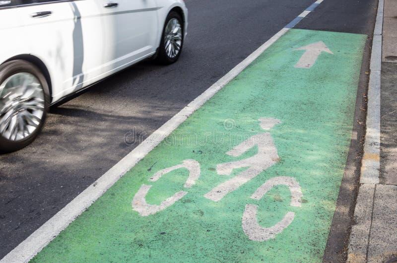 以沿一条拥挤的街的绿色标记的自行车道 免版税图库摄影