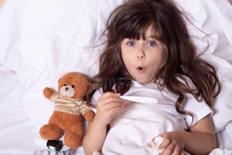 以热病和病症在床上检查温度的病的孩子与温度计 孩子流感治疗 E 免版税库存照片