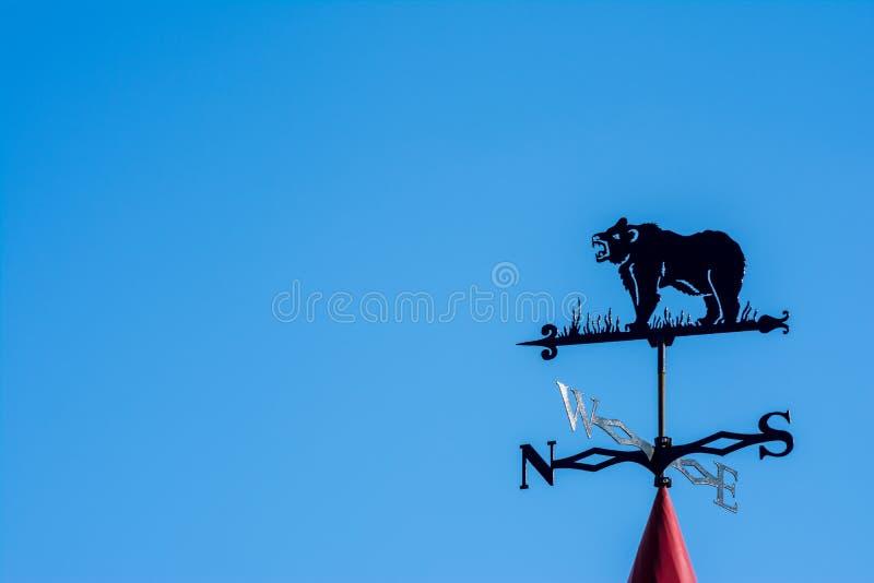 以熊的形式风标 世界的边反对天空的 免版税库存图片