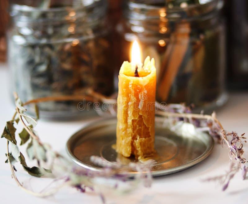 以瓶子干茶为背景是附近说谎干花和叶子的一个灼烧的蜡烛在 免版税图库摄影
