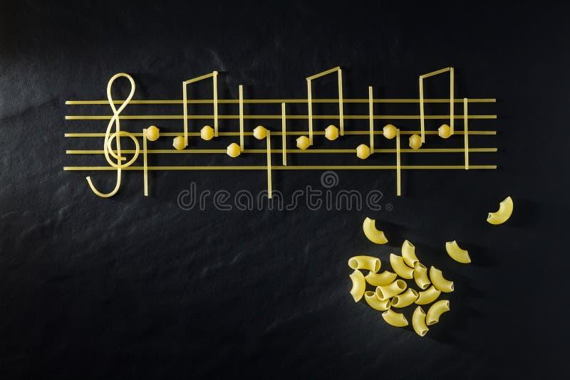 以笔记的形式音乐意大利面团,隔绝在黑质地背景 免版税库存照片