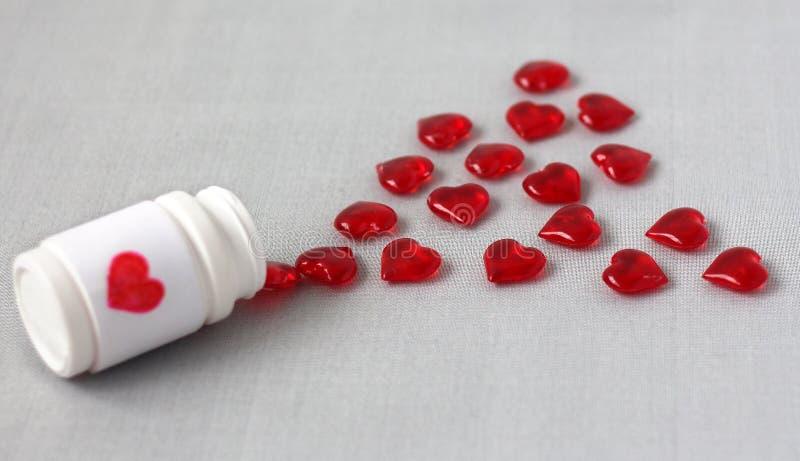 以红色心脏,从溢出的银行的形式维生素 免版税库存图片