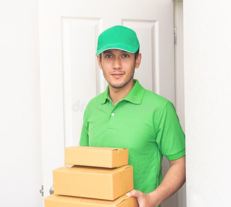 以绿色递包裹的送货人对您的门 免版税图库摄影