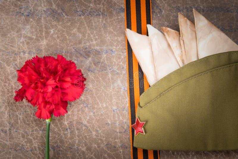 以老纸、红色康乃馨、信封、军用盖帽和圣乔治丝带,特写镜头为背景 免版税库存照片