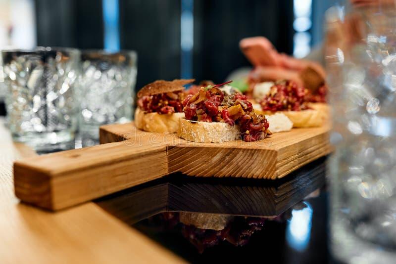 以肉bruschetta的形式开胃菜在一个木板和空的玻璃觚 免版税图库摄影