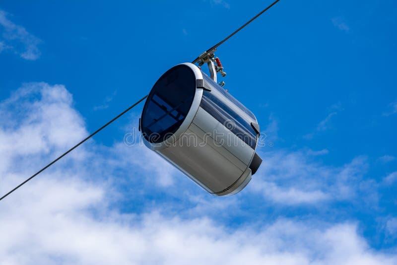以胶囊的形式,反对在电车的天空是移动的客舱 免版税库存照片