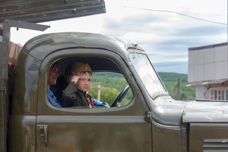 以苏联战士的形式一个小男孩在军队汽车的驾驶舱内参加游行以纪念胜利天 免版税库存图片