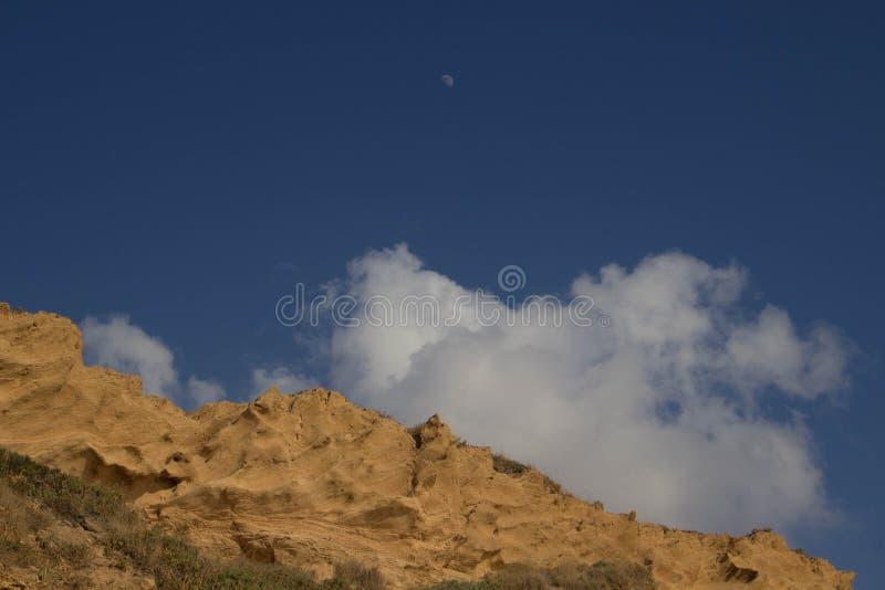 以蓝色美丽如画的天空为背景的桑迪峭壁与云彩 免版税库存图片