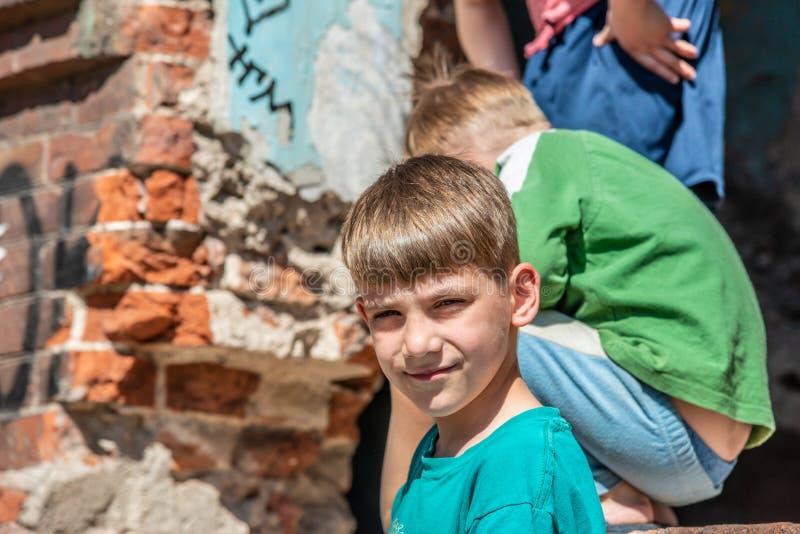 以被毁坏的大厦为背景的可怜的孤儿,街道孩子生活的概念  演出的照片 免版税图库摄影