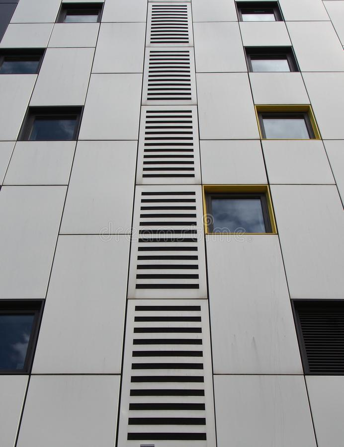 以重复窗户和几何网格设计为设计手段,将银色金属覆盖板封闭在现代建筑上 免版税库存图片