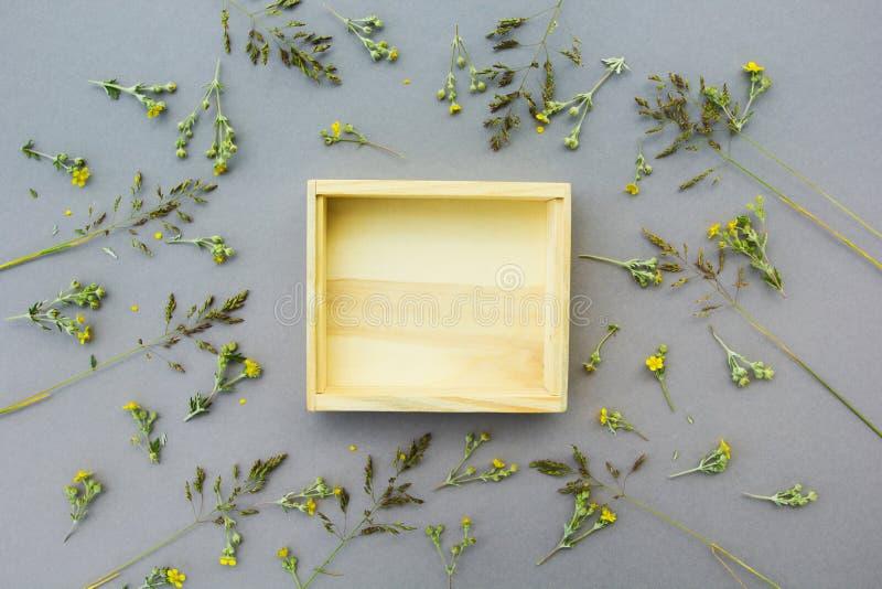 以野花为背景的一个木箱 对象或文本的一个空的地方 灰色背景 免版税库存照片