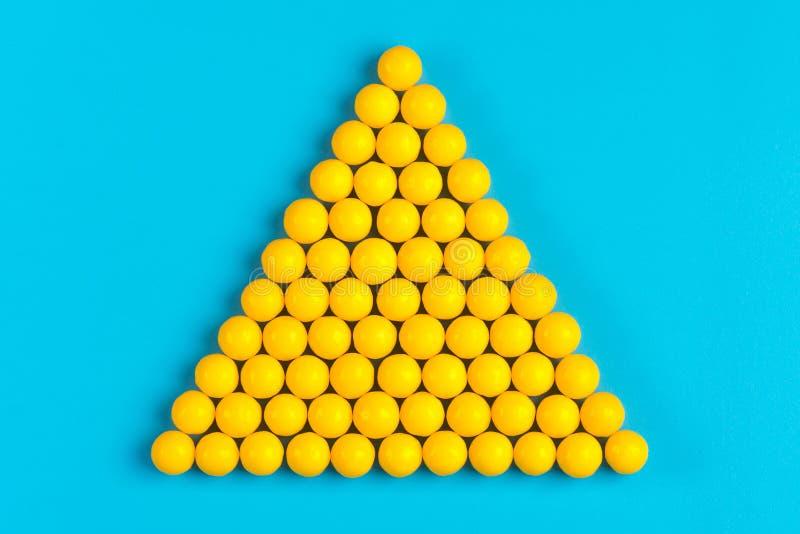 以金字塔和蓝色背景的形式,黄色药片被提出 免版税库存照片