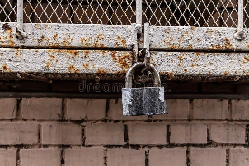 以铁箱子滤栅为背景的老被风化的闭合的灰色挂锁围住工业背景 库存图片