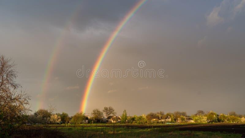 以黑暗的天空为背景的一条双重彩虹 农村的横向 免版税库存图片