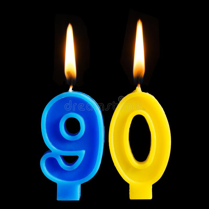 以90九十个图的形式灼烧的生日蜡烛被隔绝的蛋糕的在黑背景 庆祝birt的概念 免版税库存图片