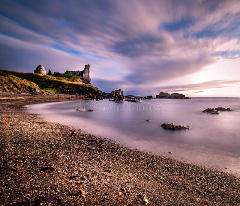 以Dunure为特色的老葡萄酒废墟海景长的曝光防御与小束的光滑的云彩和海洋 免版税库存照片