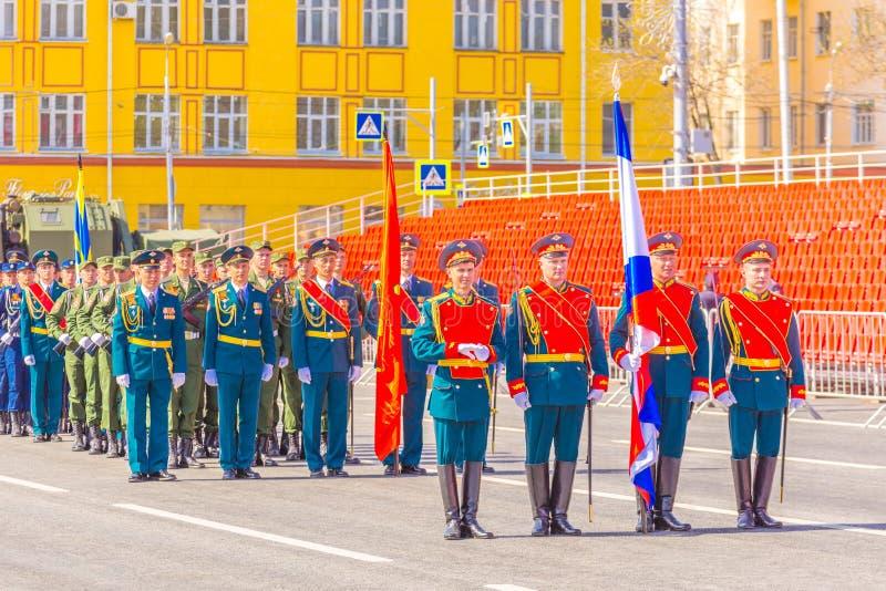仪仗队的军人运载胜利横幅和俄国三色在军事同水准的礼仪行军 图库摄影