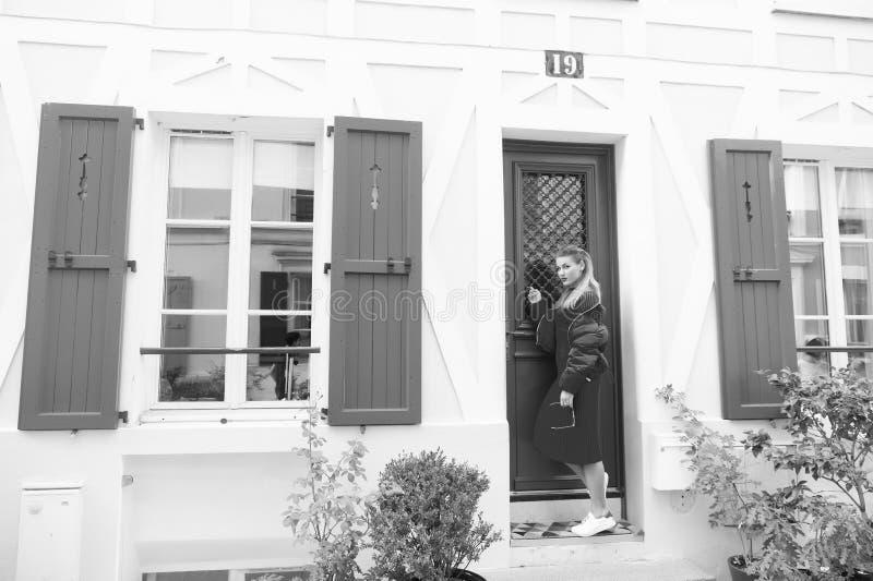 任何人在家 敲门的夫人客人等待公寓让她送进的所有者 在门附近的妇女时髦的成套装备立场 免版税图库摄影