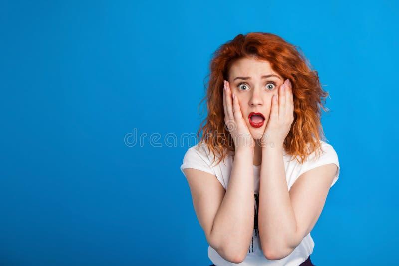 仿照废物样式的迷茫的红发女孩 情感概念 在明亮地蓝色m背景 安置文本 免版税库存照片