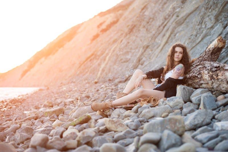 仿照bokho别致样式的梦想的孤独的深色的嬉皮坐灰色石头在落日的光芒的海岸 库存图片