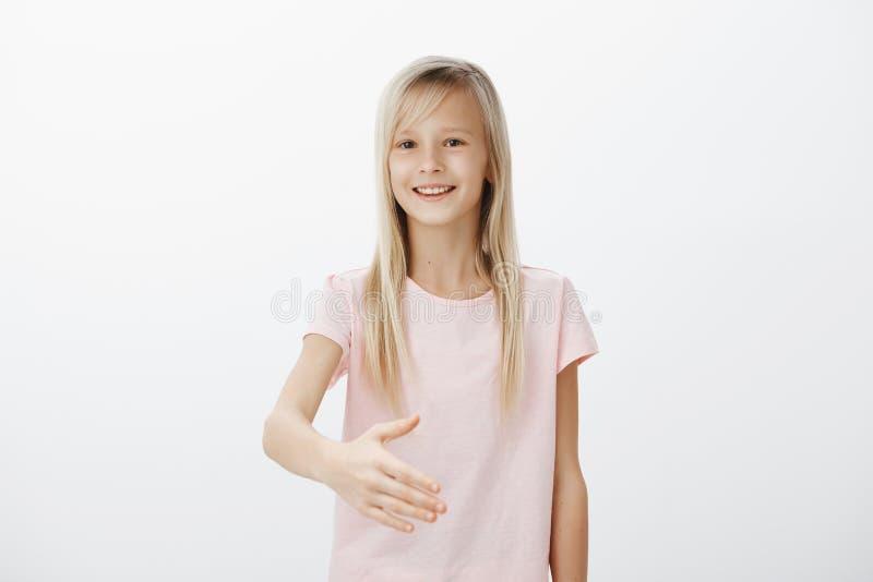 仿造父亲的女孩,学会如何给牢固的handhsake 与金发的友好的相当小女性孩子,拉扯 免版税库存照片