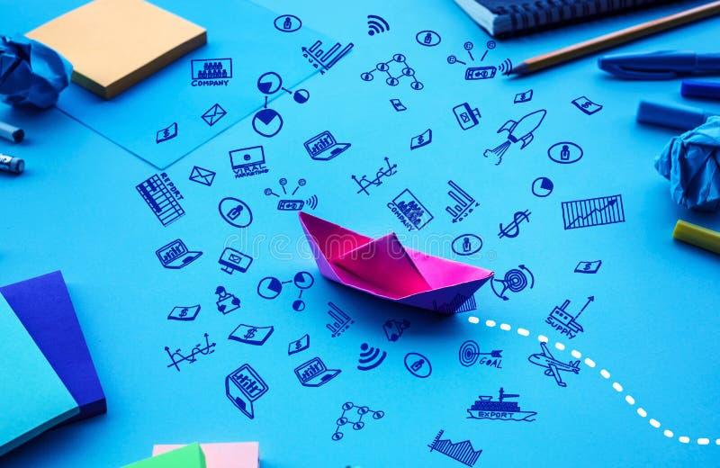 企业与小船纸和企业乱画象的方向或目标概念在工作台背景 免版税库存图片