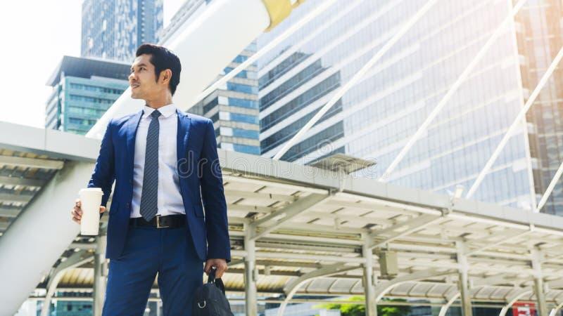 企业亚洲与纸杯的人立场画象  免版税库存照片