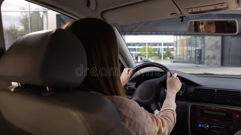 企业人坐在汽车的,女性司机,舒适的运输,后面看法 免版税库存照片