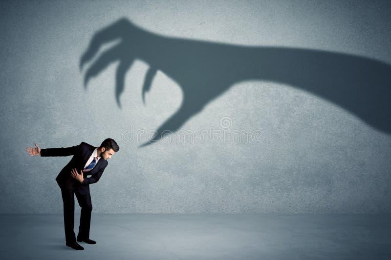 企业人害怕一个大妖怪爪阴影概念 免版税库存图片