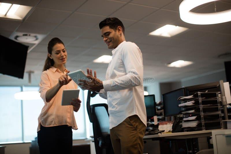 企业同事谈论在数字式片剂在办公室 图库摄影