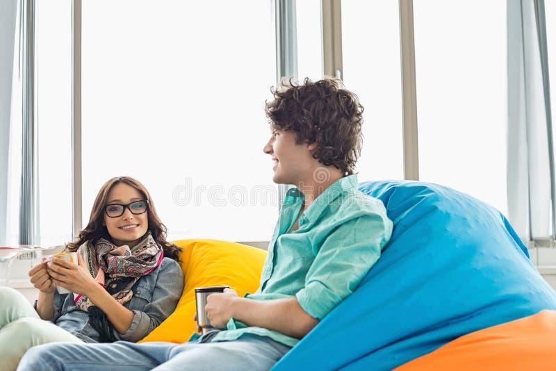 企业同事食用咖啡,当放松在装豆子小布袋椅子在创造性的办公室时 图库摄影