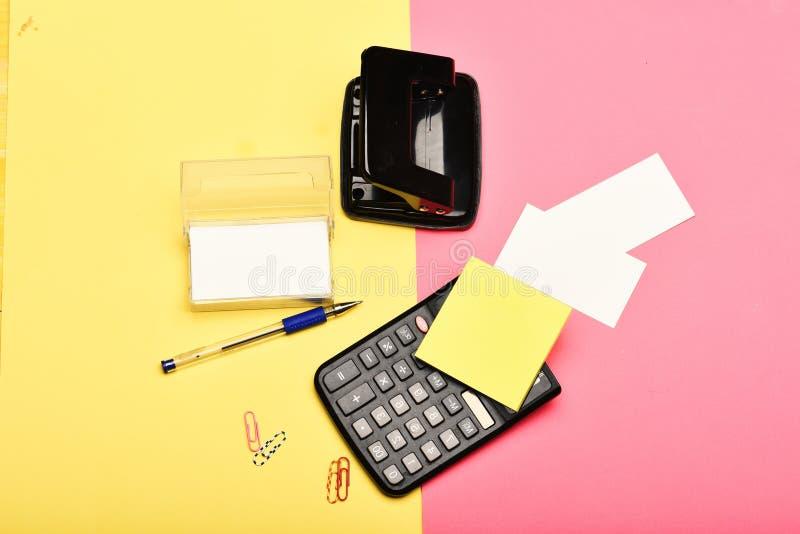 企业和工作概念 打孔器、笔、笔记、纸夹和其他办公室工具 与空白的名片持有人 库存图片