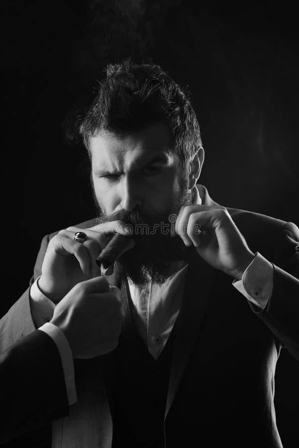企业和恶习概念 有胡子的人拿着在黑背景的雪茄 免版税库存照片