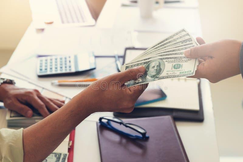 企业和财务概念,捐钱的商人的手给他的伙伴 免版税库存图片