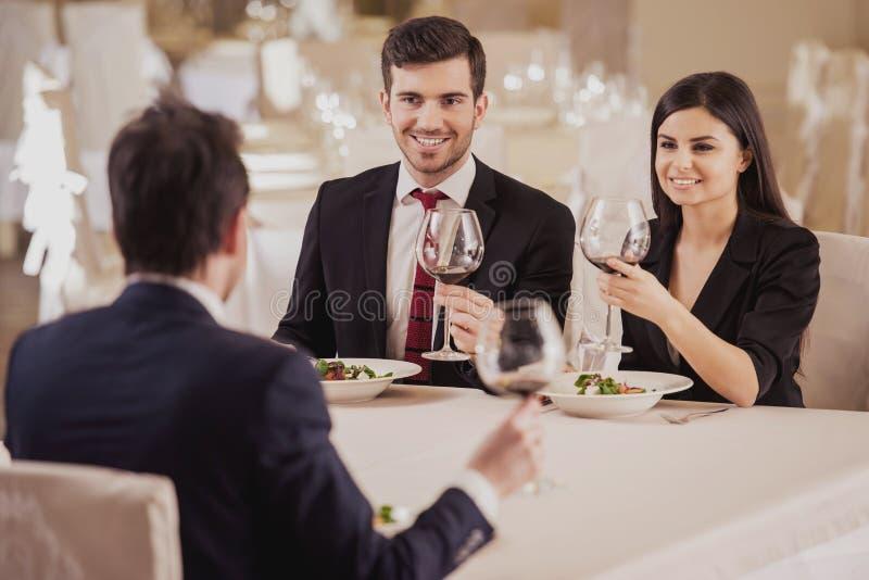 企业咖啡杯方便问题午餐开张了 在餐馆合作会议,一起吃和喝为庆祝好工作 库存照片