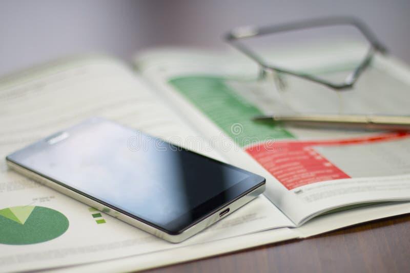企业图与手机、铅笔和玻璃的stiill生活 免版税库存照片