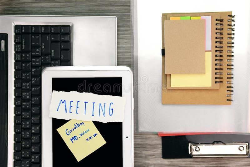 企业备忘录提醒会议 有膝上型计算机和片剂的办公桌 库存照片