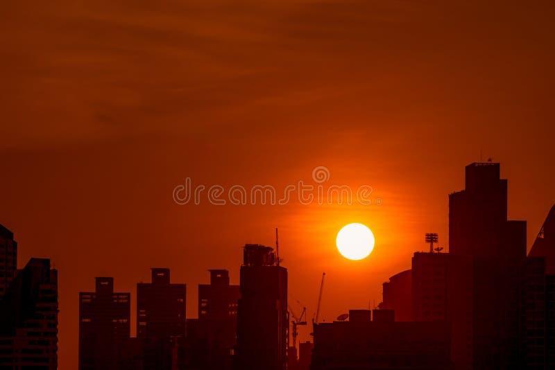 企业大厦在黄昏的街市与美丽的日落天空 公寓房和公寓剪影在晚上 r 库存图片
