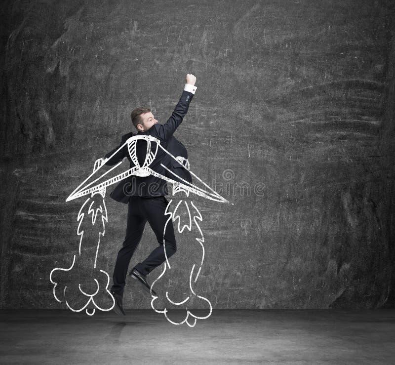 企业天使的概念 一个人飞行在黑黑板 免版税库存图片