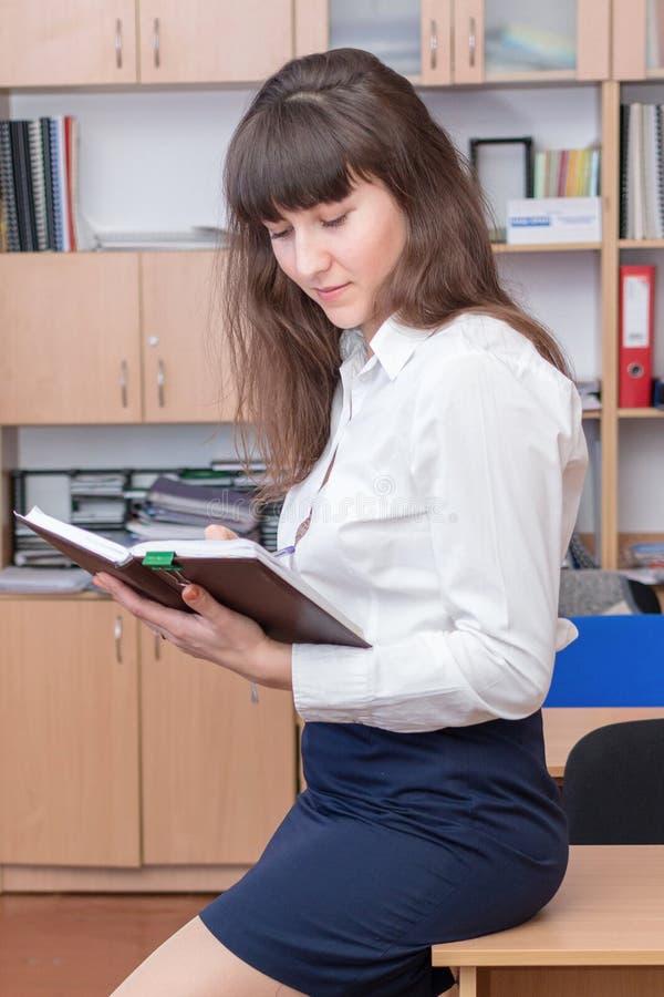 37企业夫人 年轻美丽的女孩在有文件的办公室 有美好的神色的女商人 在Th的逗人喜爱的女性画象 库存图片