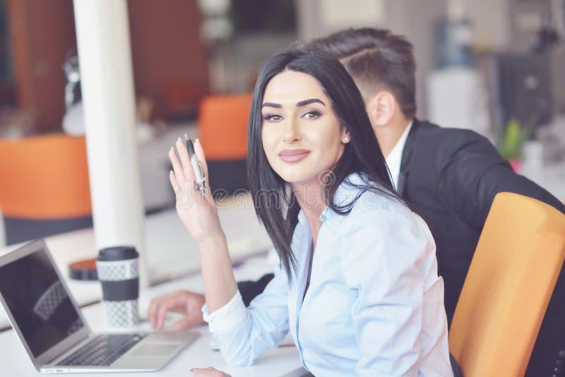 企业夫妇在研究计算机的办公室 免版税图库摄影
