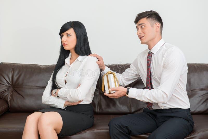 企业夫妇坐沙发在办公室 库存照片